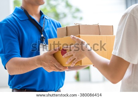 Woman hand accepting a delivery of boxes from deliveryman #380086414