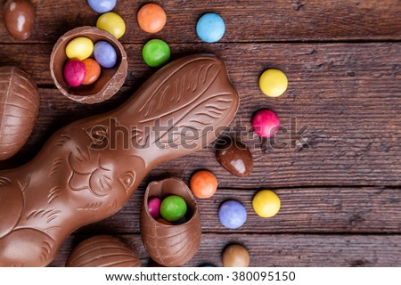 Delicious chocolate easter eggs and sweets on wooden background Royalty-Free Stock Photo #380095150