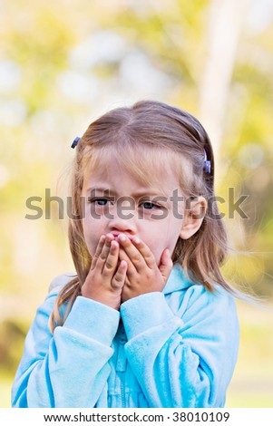 Little girl with hands over mouth and a look of shock or sadness. #38010109