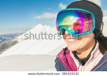 Happy girl dressed in ski or snowboard fashion mask goggles. Mountain landscape. Extreme adventure. Winter ski resort #380103532