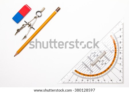 rubber eraser, pair of compasses, pencil and protractor on white paper #380128597