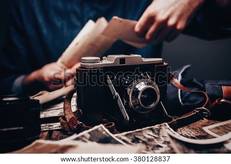 Vintage camera in front of photographer who sort photos on wooden old table