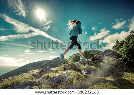 Female running in mountains under sunlight. Royalty-Free Stock Photo #380232163