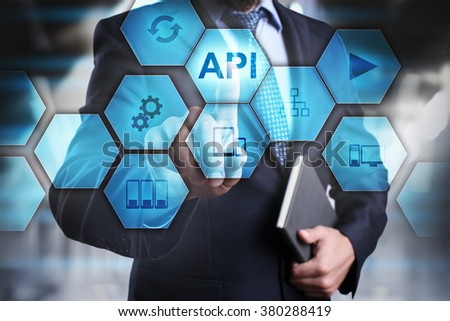 "Businessman pressing button on touch screen interface and select ""API"". Business concept. Internet and technology concept."