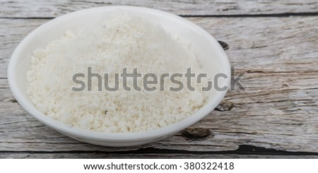 Dried coconut powder in white bowl over wooden background #380322418