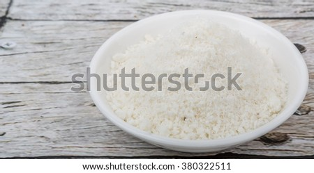Dried coconut powder in white bowl over wooden background #380322511