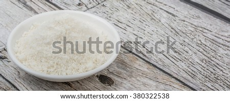 Dried coconut powder in white bowl over wooden background #380322538