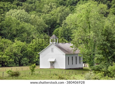 A small white church building is backed by a hillside full of green trees in rural Monroe County, Ohio. #380406928
