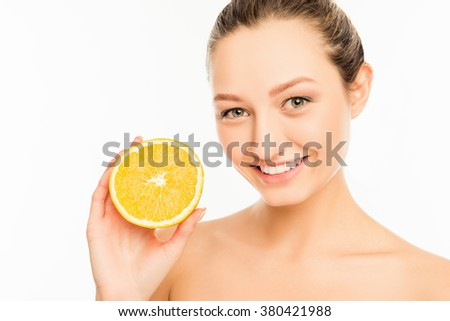 Young cute girl with nice smile and orange slice #380421988