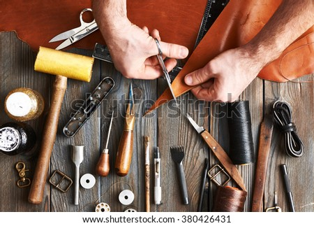Man working with leather using crafting DIY tools  Royalty-Free Stock Photo #380426431