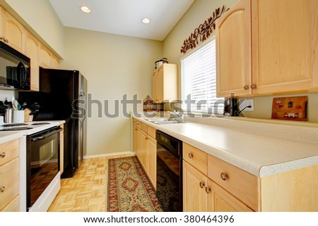 Simple kitchen with hardwood floor ad black fridge. #380464396