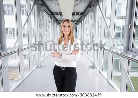 Businesswoman standing in a modern Building with a white shirt and black pants #380682439