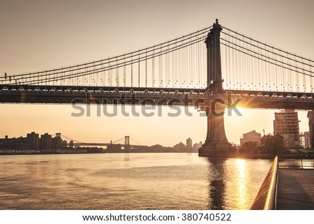 Tranquil sunset behind Brooklyn Bridge with a sunburst below the span silhouetting the tower and suspension cables above the water of the East River #380740522