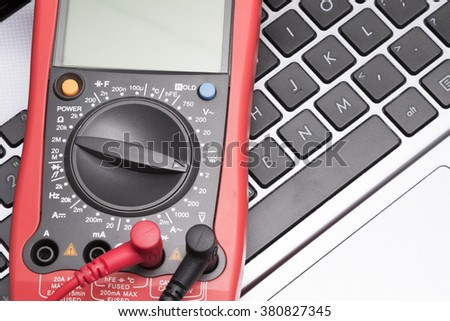 Multimeter and laptop. Red digital multimeter on the laptop background. Selective focus with shallow depth of field.