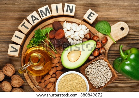 Foods rich in vitamin E such as wheat germ oil, dried wheat germ, dried apricots, hazelnuts, almonds, parsley leaves, avocado, walnuts, pumpkin seeds, sunflower seeds, spinach and green paprika  #380849872