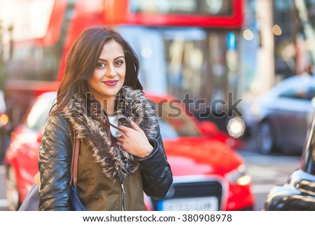 Indian girl portrait in London. She is standing by a busy road with blurred traffic on background. There are cars and red buses. She is smiling and looking at camera. Travel and lifestyle concepts #380908978