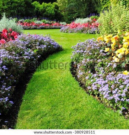 Colorful Flowers and a Winding Grass Lawn Path in a Beautiful Garden #380928511
