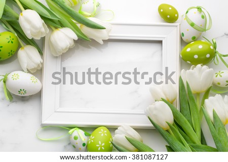 Tulip,easter eggs and blank picture frame on white marble background