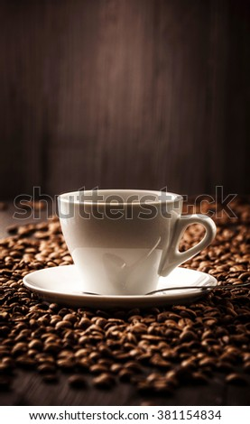 Cup fragrant coffee on beans background with spoon #381154834