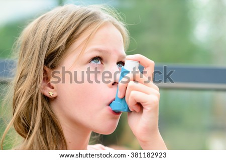 Girl having asthma allergy using the asthma inhaler for being healthy - shallow depth of field Royalty-Free Stock Photo #381182923