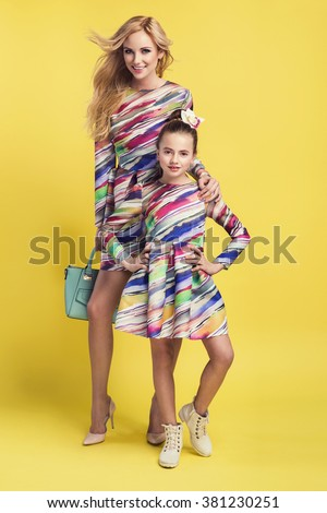 Fashion woman and a pretty little girl wearing the same colorful dresses. Photo of mother and daughter #381230251