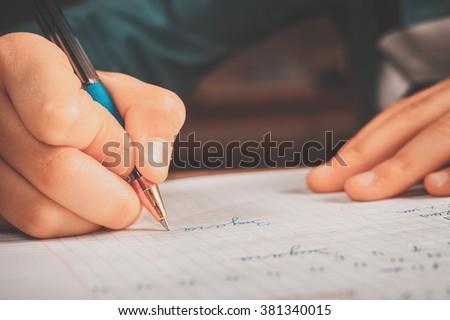 Schoolgirl doing homework. #381340015