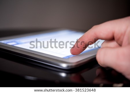 Tablet being used at night for business in a dark room #381523648