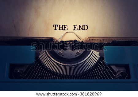 closeup of a blue retro typewriter and the text the end written with it in a yellowish foil Royalty-Free Stock Photo #381820969