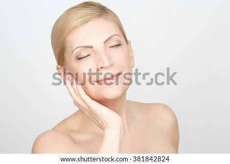 Smooth as silk. Horizontal portrait of a beautiful mature woman touching her face smiling with her eyes closed #381842824