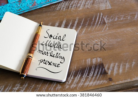 Retro effect and toned image of notebook next to a fountain pen. Business concept image with handwritten text SOCIAL MEDIA MARKETING PRESENCE , copy space available
