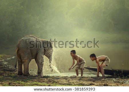 Two boys are playing splashing water with baby elephant at pond #381859393