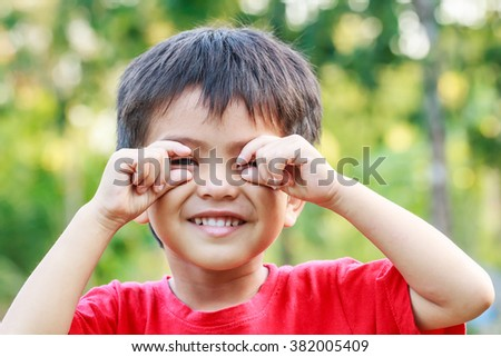 Portrait of smiling little young Asian boy in nature #382005409