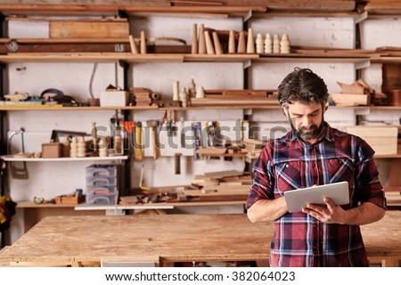 Artisan woodwork studio with shelving holding pieces of wood, with a carpenter standing in his workshop using a digital tablet Royalty-Free Stock Photo #382064023