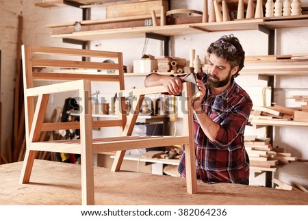 Serious furniture designer carefully sanding a chair frame that he is busy manufacturing in his woodwork studio, with shelves of wooden items behind him Royalty-Free Stock Photo #382064236