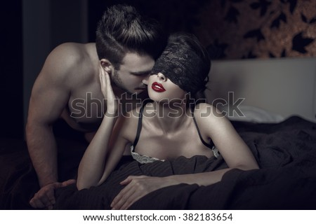 Sexy woman in lace eye cover and red lips with young lover, foreplay  #382183654