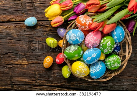 Easter eggs and tulips on wooden planks Royalty-Free Stock Photo #382196479