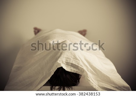 Corpse of a Person Lying on the Table Inside a Morgue with White Cloth Cover. Royalty-Free Stock Photo #382438153