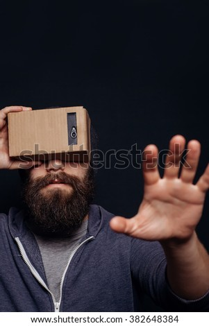 Color shot of a young man looking through a card board, a device with which one can experience virtual reality on a mobile phone. man touches the hand. blurry photos #382648384