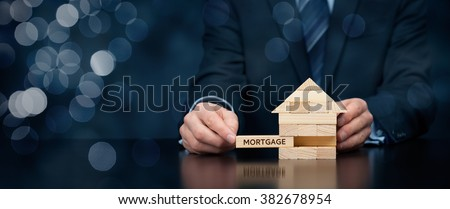 Mortgage concept. Financial agent complete wooden model of the house with last piece with text mortgage. Wide banner composition with bokeh background. #382678954