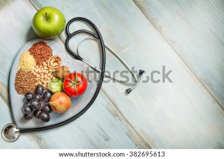 Healthy lifestyle and healthcare concept with food, heart and stethoscope Royalty-Free Stock Photo #382695613