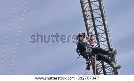 CAABIYA, ISRAEL - FEBRUARY 10, 2016: Firefighter from Northern Israel Fire Brigade drop from crane during drill under blue sky, to increase awareness of Arab kids to risks of fire #382707349