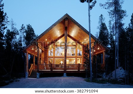 Exterior view of a modern log cabin at night.