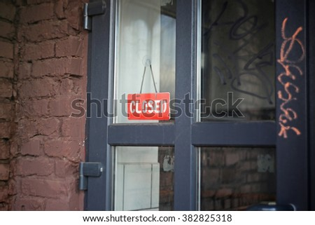 Red closed sign on the glass door of the industrial building #382825318
