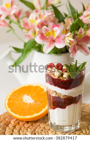 Homemade parfait served in high glasses with yogurt and organic raspberries, nuts and mint. Delicious snack for healthy life.  Breakfast on a straw tablemat with spoons and flowers and half of orange #382879417