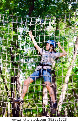 adventure climbing high wire park - people on course in mountain helmet and safety equipment #382881328