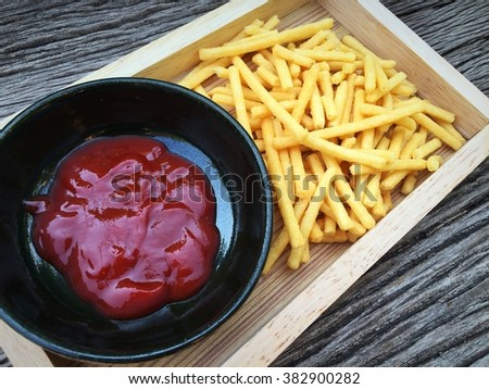 French-fries with ketchup on wood box #382900282