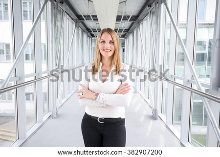 Businesswoman standing in a modern Building with a white shirt and black pants #382907200