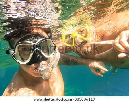 Adventurous best friends taking selfie snorkeling underwater - Adventure travel lifestyle enjoying happy fun moment - Trip together around Philippines wonders - Soft focus due to water density #383036119