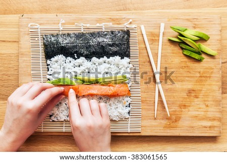 Preparing sushi. Salmon, avocado, rice on seaweed and chopsticks on wooden table. View from the top. #383061565