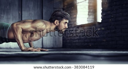 Sport. Young athletic man doing push-ups. Muscular and strong guy exercising. #383084119